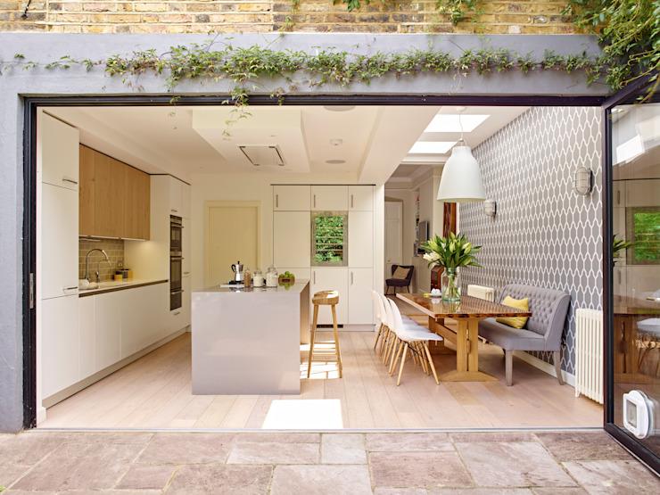 Cuisine, salle à manger et portes pliantes ouvrant sur le jardin Holloways of Ludlow Bespoke Kitchens & Cabinetry Modern kitchen Wood White