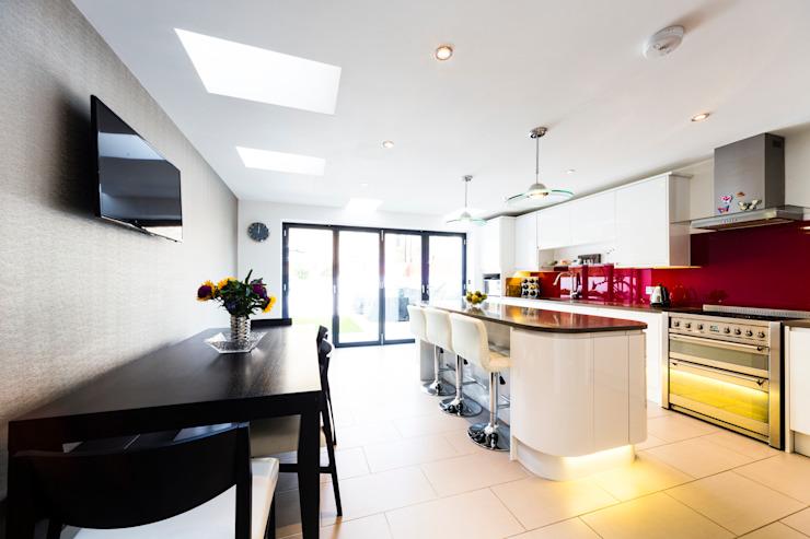 Cuisine blanche avec dosseret rouge, pendentifs de cuisine modernes, portes pliantes, table et chaises noires Cuisine moderne par Affleck Property Services Modern