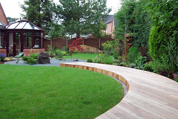 Une terrasse incurvée relie la zone des sièges à la maison Lush Garden Design Jardin de style asiatique