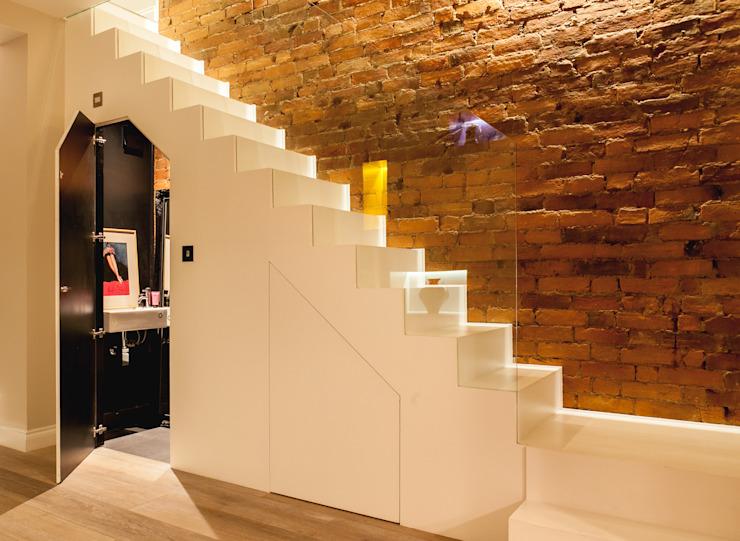 Escalier blanc minimaliste avec mur en briques apparentes et vestiaire dissimulé Timothy James Interiors Stairs